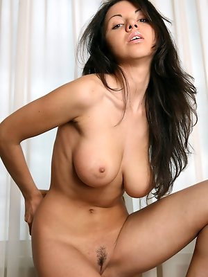 Aurora A flaunts her sexy, naked body with large puffy tits and trimmed pussy on the chair.